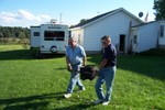 Al & Jim start carrying the empty heavy iron kettles down to the fire pit