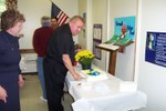 Father Frank cuts his cake as Jeannette Wills looks on - Picture 3655