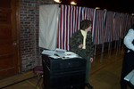 Donna Meunier takes one last check to insure there is no one left in the booths before closing down the voting machine